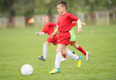 Calcio di calcio dei bambini - i giocatori dei bambini abbinano sul campo di calcio fotografia stock libera da diritti