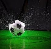 Calcio di calcio sulla spruzzatura dell'uso dell'acqua per il fondo dell'attrezzatura della palla di sport Immagini Stock