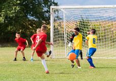 Calcio di calcio dei bambini - i giocatori dei bambini abbinano sul campo di calcio immagine stock libera da diritti