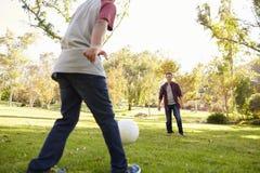 Calcio di respinta del ragazzo di sette anni al suo papà in parco, il raccolto Immagine Stock