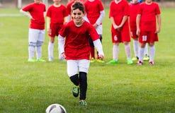 Calcio di respinta del ragazzo sul campo sportivo Immagini Stock Libere da Diritti