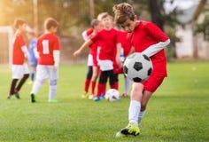 Calcio di respinta del ragazzo sul campo sportivo Fotografia Stock