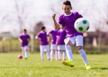 Calcio di respinta del ragazzo sul campo sportivo Fotografia Stock Libera da Diritti