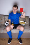 Calcio di sorveglianza del giovane sulla TV a casa e mostrando cartellino rosso Fotografie Stock Libere da Diritti