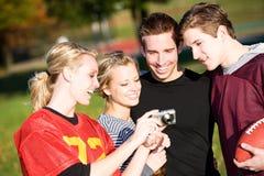 Calcio: Sguardo degli amici all'immagine divertente sulla macchina fotografica fotografia stock