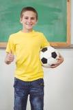 Calcio sorridente della tenuta dell'allievo in un'aula Immagini Stock Libere da Diritti