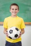 Calcio sorridente della tenuta dell'allievo in un'aula Immagini Stock