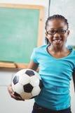Calcio sorridente della tenuta dell'allievo in un'aula Immagine Stock