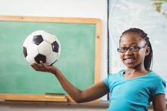 Calcio sorridente della tenuta dell'allievo in un'aula Immagine Stock Libera da Diritti