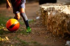 Calcio su erba con la famiglia che sta intorno all'aperto nel parco Gambe del ragazzino circa da giocar a calcioe con il suo immagine stock libera da diritti
