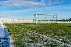 Calcio vuoto & x28; Soccer& x29; Campo nell'inverno coperto parzialmente in neve - Sunny Winter Day immagine stock