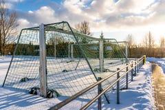 Calcio vuoto ( Soccer) Campo nell'inverno coperto parzialmente in neve - Sunny Winter Day fotografia stock libera da diritti