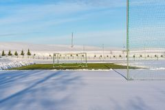 Calcio vuoto ( Soccer) Campo nell'inverno coperto parzialmente in neve - Sunny Winter Day immagine stock