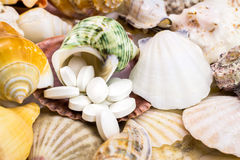 Calcium natural food supplement pills on the beautiful seashells background Stock Photo