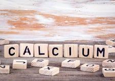 Calcium van houten brieven op houten achtergrond stock afbeelding