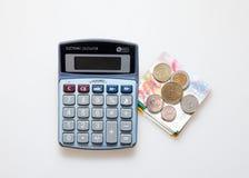 Calcolatore, banconote israeliane dello shekel e monete isolati su bianco immagini stock