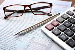 Calcolatore con i documenti ed i vetri sulla tavola immagini stock libere da diritti