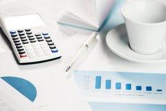 Calcolatore con i grafici finanziari su una tavola con la tazza del coffe fotografie stock