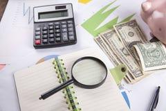 Calcolatore con soldi ed il porcellino salvadanaio sullo scrittorio fotografia stock