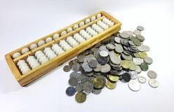 Calcolatore dell'abaco cinese con le monete dei soldi fotografia stock