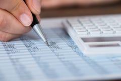 Calcolatore di Person Hands With Pen And sopra il rapporto Fotografia Stock Libera da Diritti