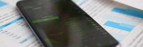 Calcolatore di Smartphone e statistiche finanziarie Fotografia Stock