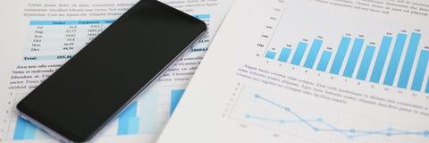 Calcolatore di Smartphone e statistiche finanziarie Fotografia Stock Libera da Diritti