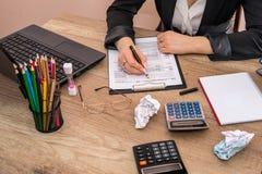 calcolatore di uso della donna con il computer portatile per il riempimento della tassa 1040 Immagini Stock