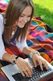 Calcolatore digitante che si siede nel giardino Fotografia Stock