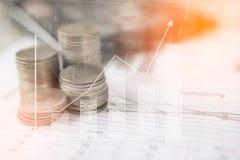 Calcolatore e moneta, i soldi con i grafici commerciali ed i grafici riferiscono sulla tavola, calcolatore sullo scrittorio di pi fotografie stock libere da diritti