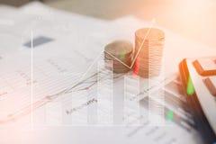 Calcolatore e moneta, i soldi con i grafici commerciali ed i grafici riferiscono sulla tavola, calcolatore sullo scrittorio di pi Immagine Stock