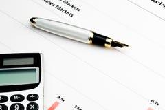 Calcolatore e penna sul diagramma finanziario Fotografia Stock