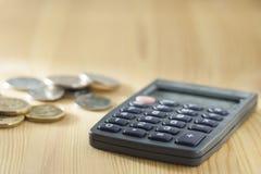 Calcolatore e una pila di monete Immagini Stock