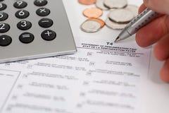 Calcolatore, modulo di imposta, penna e monete Fotografia Stock