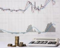 Calcolatore, monete e grafico economico Fotografia Stock