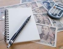 Calcolatore, taccuino e matita su valuta di Yen giapponesi Fotografie Stock Libere da Diritti