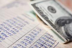 Calcoli e 100 banconote in dollari immagine stock