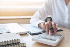 Calcoli femminili del ragioniere ed analizzare il dat finanziario del grafico immagine stock