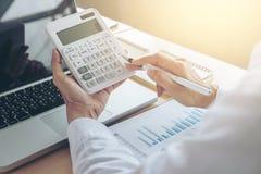 Calcoli femminili del ragioniere ed analizzare il dat finanziario del grafico fotografie stock