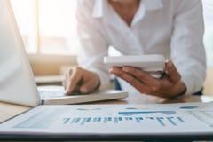 Calcoli femminili del ragioniere ed analizzare il dat finanziario del grafico fotografia stock