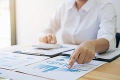 Calcoli femminili del ragioniere ed analizzare il dat finanziario del grafico immagini stock
