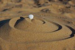 Calcoli la piramide dei riccioli sulla sabbia calda sciolta, coperture bianche sulla cima fotografia stock