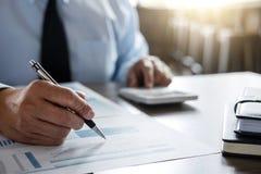 Calcoli maschii del ragioniere ed analizzare i dati finanziari del grafico fotografie stock libere da diritti