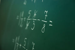 Calcualting with fractions. On green blackboard at primary school Royalty Free Stock Photo
