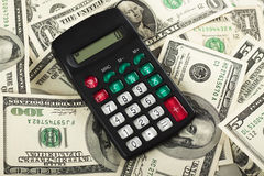 Calcuator. A small black calculator on a pile of dollar bills Royalty Free Stock Images