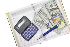 Calculadora, billetes de banco del dólar, pluma y cuaderno en un blanco fotografía de archivo libre de regalías