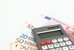 Calculadora, billetes euro y monedas euro aislados en blanco Fotografía de archivo