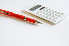 Calculadora branca e pena vermelha. Fotos de Stock