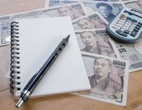 Calculadora, caderno e lápis na moeda do iene japonês Fotos de Stock Royalty Free