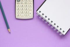 Calculadora, caderno e lápis no fundo lilás fotografia de stock royalty free